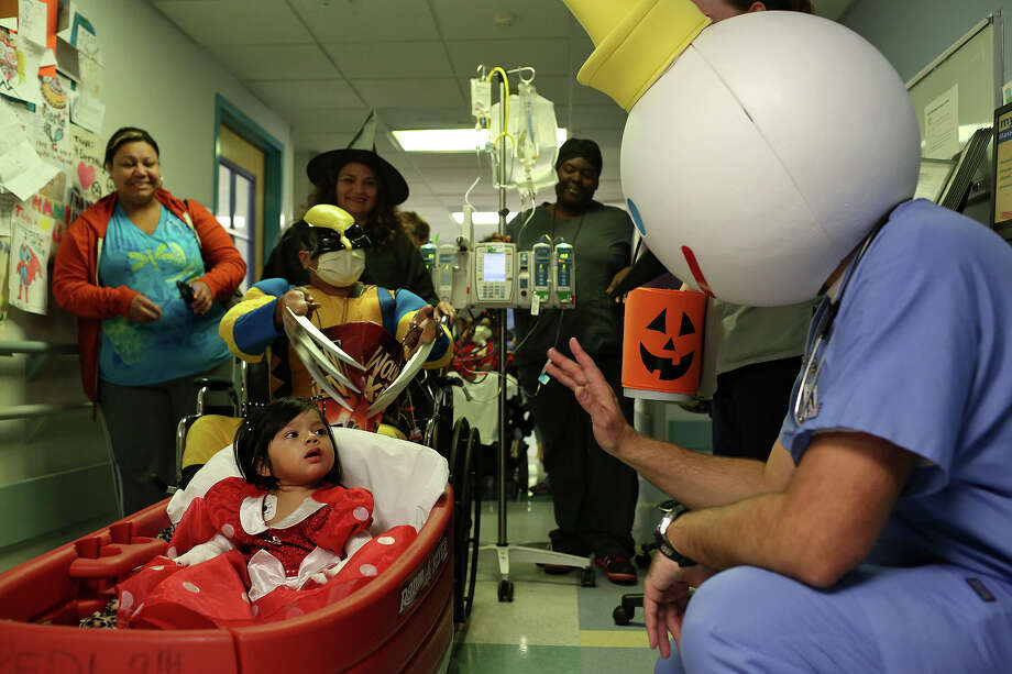 "Staff Sgt. Craig Chase, a flight paramedic dressed as ""Dr. Jack,"" right, waves to patient Nevaeh Betancourt, 1, followed by patient Max Ruiz, 11, during the Pediatric Halloween Parade at University Hospital on Thursday, Oct. 31, 2013. Photo: Lisa Krantz, San Antonio Express-News / San Antonio Express-News"