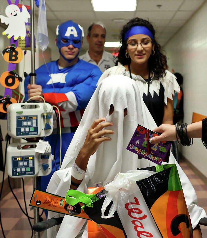 Patient David Serna, 15, is pushed by volunteers Kiabeth Huerta, 18, and Gregorio Contreras, 17, as they make their way through the halls of University Hospital during the Pediatric Halloween Parade on Thursday, Oct. 31, 2013. Photo: Lisa Krantz, San Antonio Express-News / San Antonio Express-News