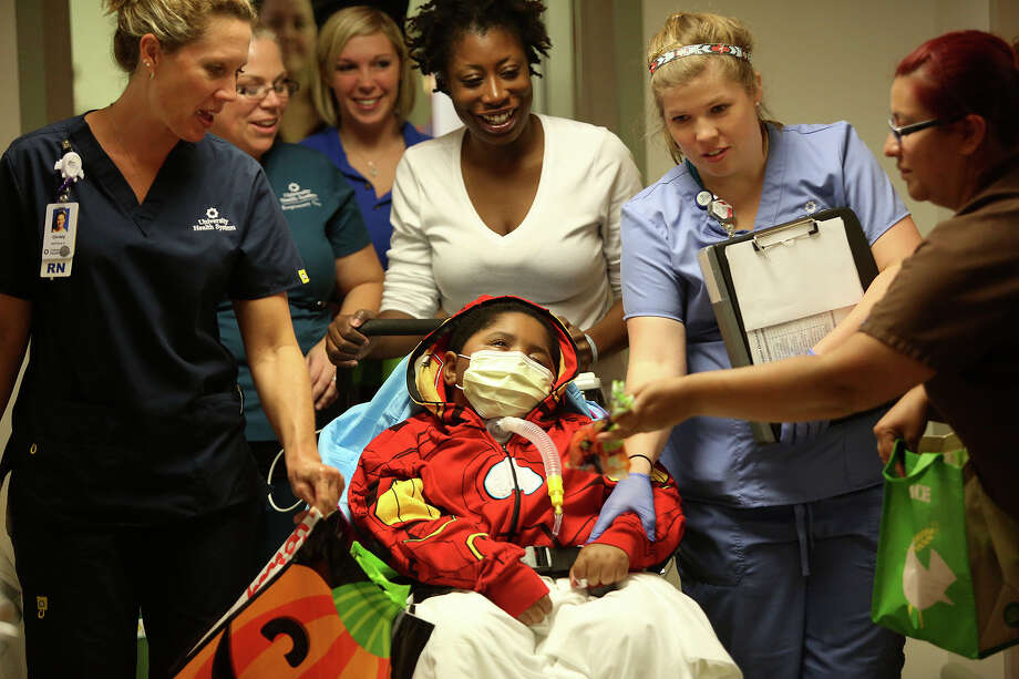 Joshawn Thomas, 8, dressed as Ironman, is pushed by his mother, Toree Anderson, with hospital staff during the Pediatric Halloween Parade at University Hospital on Thursday, Oct. 31, 2013. Photo: Lisa Krantz, San Antonio Express-News / San Antonio Express-News