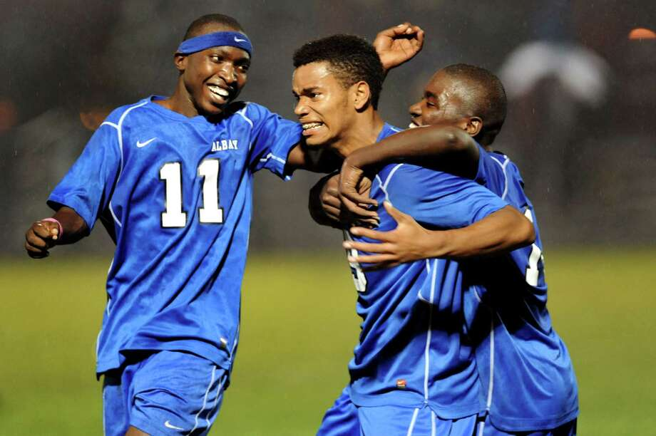 Albany teammates celebrate with Khalid Holtzclaw, center, after he scores in their Section II Class AA soccer semifinal on Thursday, Oct. 31, 2013, at Colonie High in Colonie, N.Y. The goal in the final minutes made the score 2-1. (Cindy Schultz / Times Union) Photo: Cindy Schultz / 00024412A