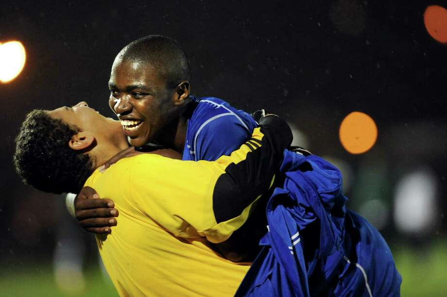 Albany's Abdullah Shakir, left, lifts teammate Immanuel Ishiwe as they celebrate their 2-1 win over Shenendehowa in the Section II Class AA soccer semifinal on Thursday, Oct. 31, 2013, at Colonie High in Colonie, N.Y. (Cindy Schultz / Times Union) Photo: Cindy Schultz / 00024412A