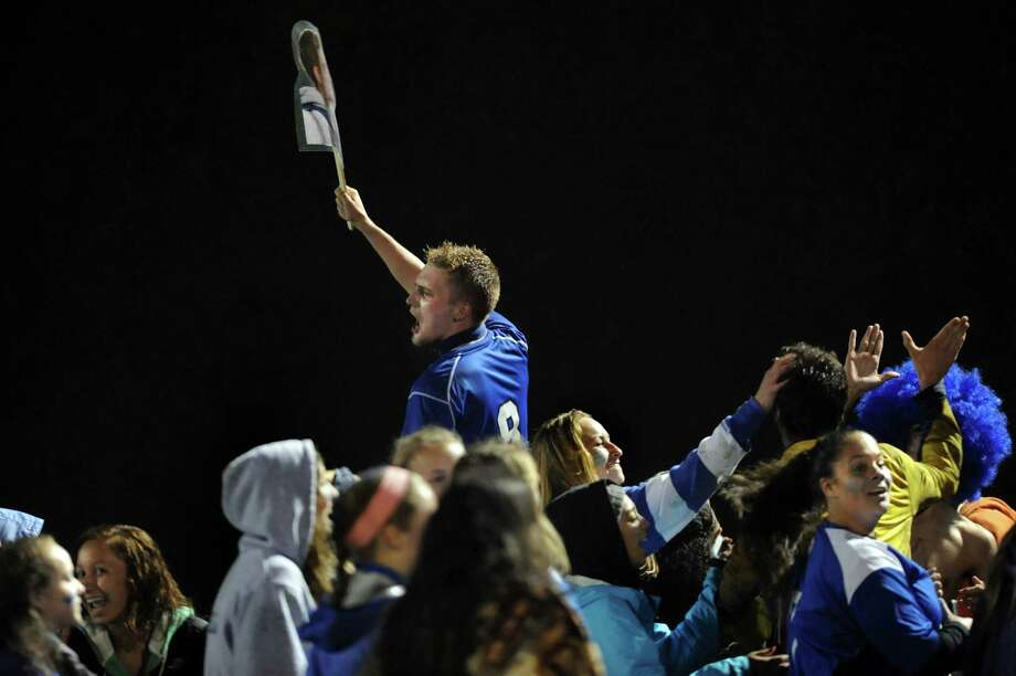 Albany fans lift Denis Leon, center, as they celebrate their 2-1 win over Shenendehowa in the Section II Class AA soccer semifinal on Thursday, Oct. 31, 2013, at Colonie High in Colonie, N.Y. (Cindy Schultz / Times Union) Photo: Cindy Schultz / 00024412A