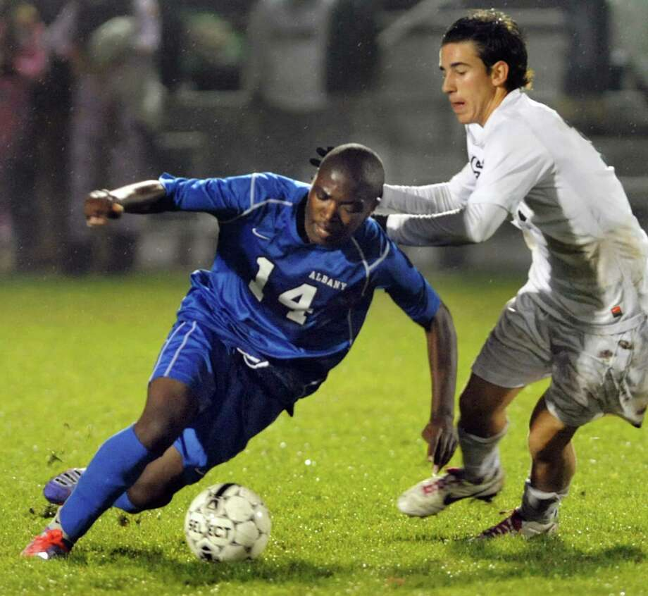 Albany's Immanuel Ishiwe, left, works the ball as Shenendehowa's Austin Hughes defends during their Section II Class AA soccer semifinal on Thursday, Oct. 31, 2013, at Colonie High in Colonie, N.Y. (Cindy Schultz / Times Union) Photo: Cindy Schultz / 00024412A