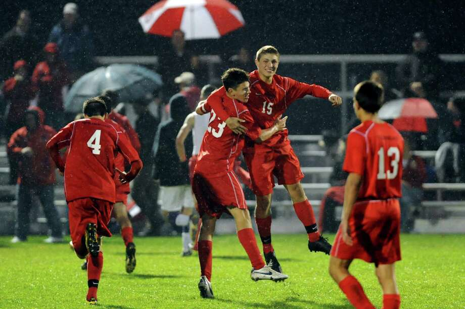 Guilderland's Matt Schiller, center, and Issac Obwald, second from right, and their team celebrate winning the Section II Class AA soccer semifinal against Shaker on Thursday, Oct. 31, 2013, at Colonie High in Colonie, N.Y. (Cindy Schultz / Times Union) Photo: Cindy Schultz / 00024412A