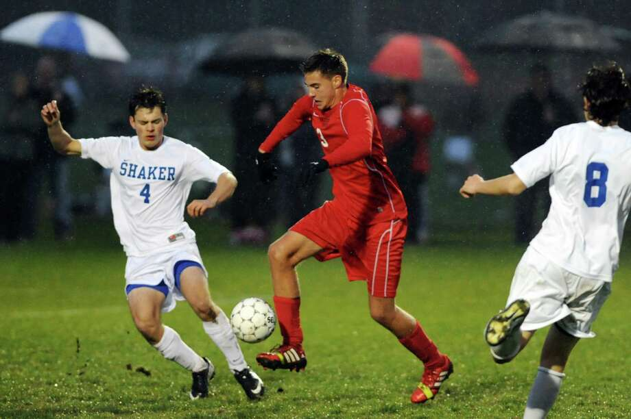 Guilderland's Chris Connolly, center, controls the ball as Shaker's Josh Catrine, left, and Brett Gaughan defend during their Section II Class AA soccer semifinal on Thursday, Oct. 31, 2013, at Colonie High in Colonie, N.Y. (Cindy Schultz / Times Union) Photo: Cindy Schultz / 00024412A