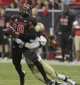 Houston wide receiver Demarcus Ayers, left, is tackled by South Florida defensive back Brandon Salinas during the first half of an NCAA college football game Thursday, Oct. 31, 2013, in Houston. (AP Photo/Houston Chronicle, James Nielsen) MANDATORY CREDIT Photo: James Nielsen, Associated Press