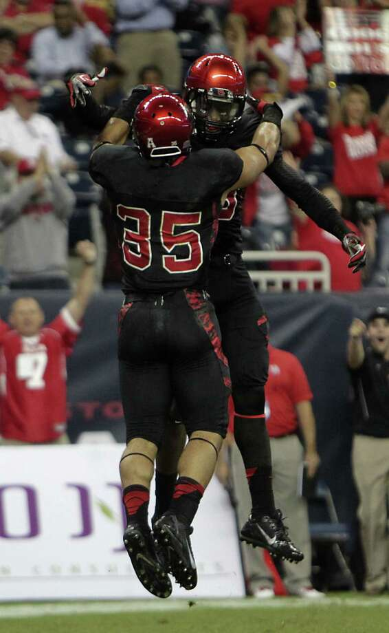 Houston running back Kenneth Farrow (35) celebrates with Xavier Maxwell after scoring on a touchdown catch in the first quarter Thursday against visiting South Florida. Farrow added a TD run in the fourth quarter of the Cougars' victory. Photo: James Nielsen / Houston Chronicle