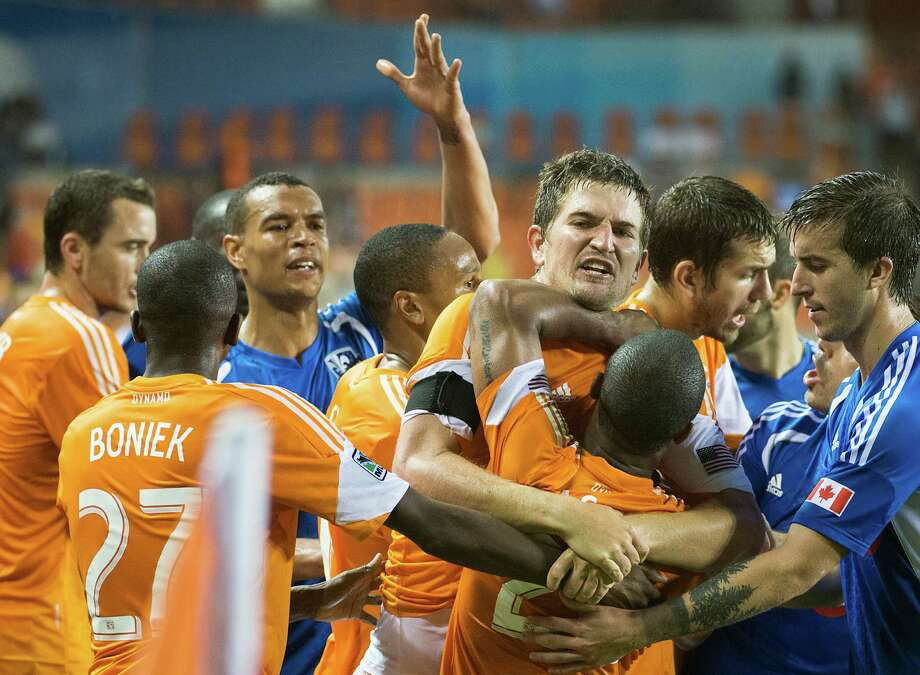 Dynamo defender Bobby Boswell restrains teammate Corey Ashe as players scuffle late in the second half. Photo: Smiley N. Pool, Houston Chronicle / © 2013  Houston Chronicle
