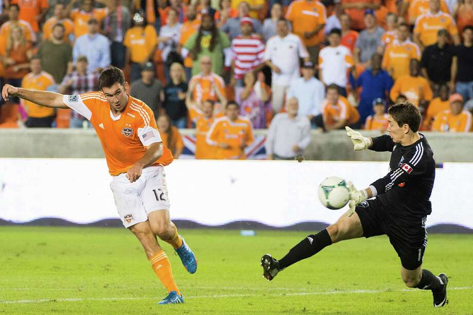 Dynamo forward Will Bruin (12) puts the ball past Montreal goalkeeper Troy Perkins to score in the 72nd minute. Photo: Smiley N. Pool, Houston Chronicle / © 2013  Houston Chronicle