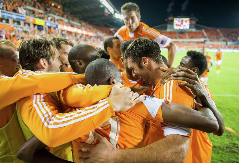 Houston players mob Will Bruin, right, after he scored his second goal of the game to put the Dynamo up by a 3-0 score. Photo: Smiley N. Pool, Houston Chronicle / © 2013  Houston Chronicle
