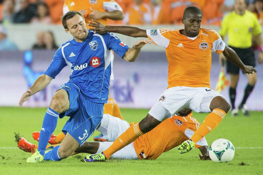 Dynamo midfielder Boniek Garcia (27) fights for the ball against Montreal midfielder Andrew Wenger (33). Photo: Smiley N. Pool, Houston Chronicle / © 2013  Houston Chronicle