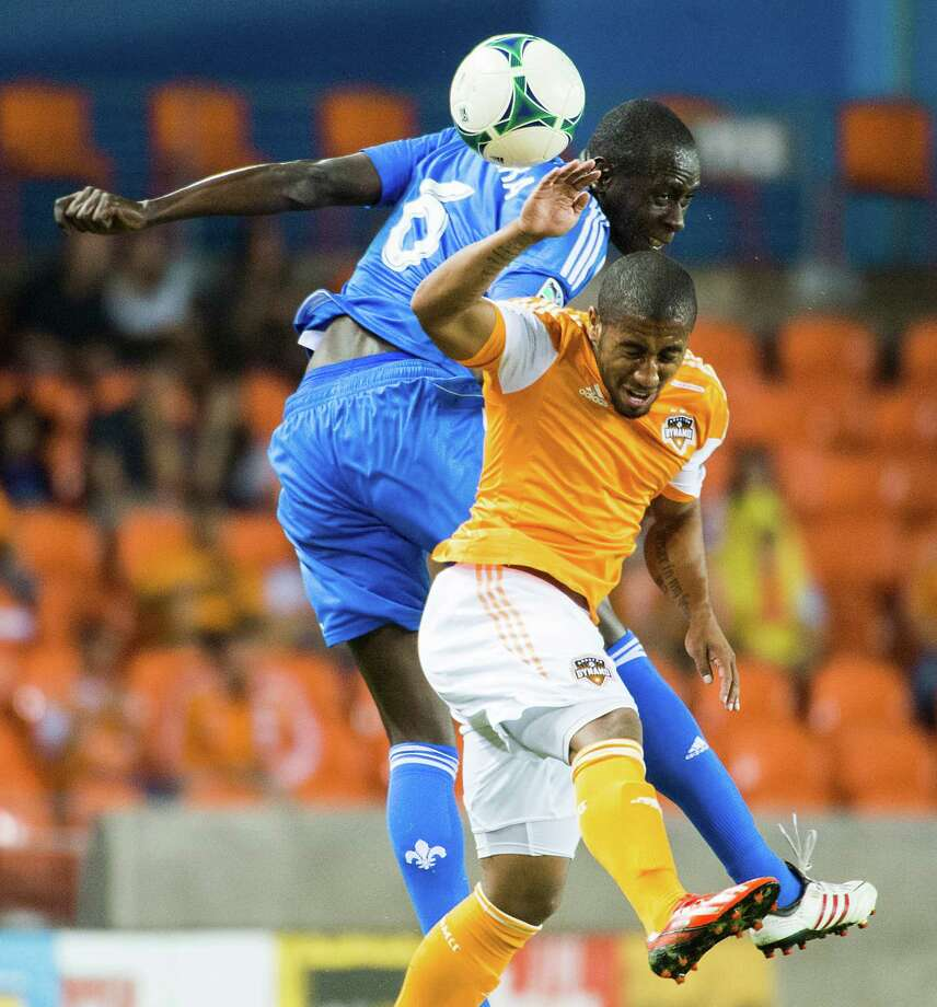 Dynamo midfielder Corey Ashe goes up for a header against Impact defender Hassoun Camara. Photo: Smiley N. Pool, Houston Chronicle / © 2013  Houston Chronicle