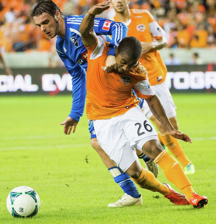 Dynamo midfielder Corey Ashe fights for the ball against Impact midfielder Andrea Pisanu. Photo: Smiley N. Pool, Houston Chronicle / © 2013  Houston Chronicle