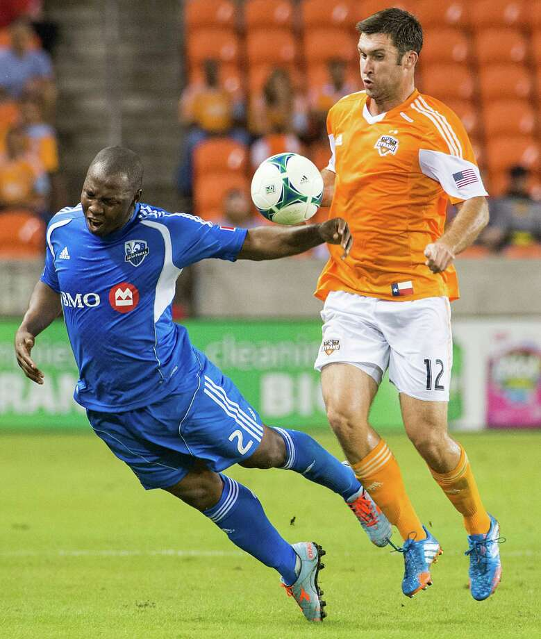 Dynamo forward Will Bruin collides with Impact defender Nelson Rivas. Photo: Smiley N. Pool, Houston Chronicle / © 2013  Houston Chronicle