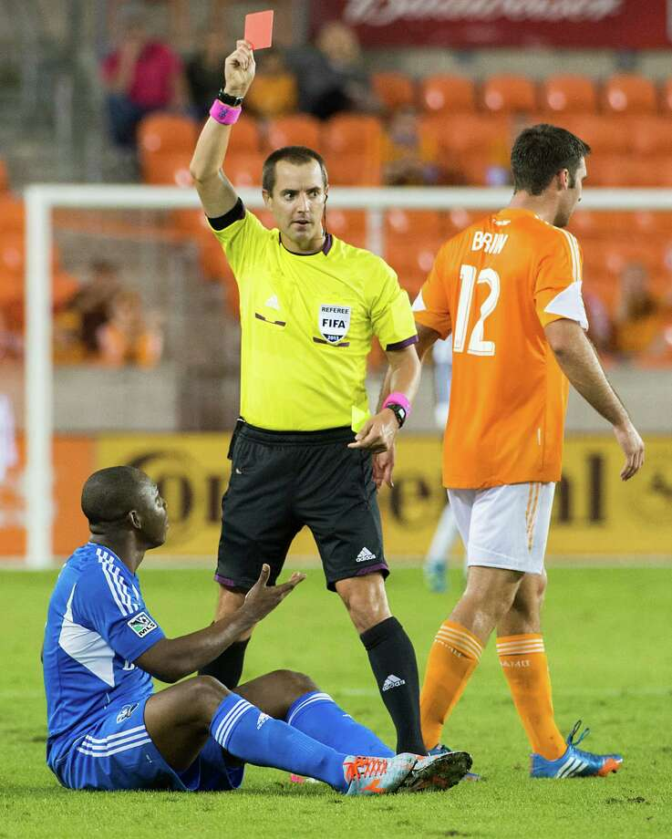 Referee Mark Geiger pulls out a red card after = Impact defender Nelson Rivas, bottom, fouled Houston Dynamo forward Will Bruin. Photo: Smiley N. Pool, Houston Chronicle / © 2013  Houston Chronicle