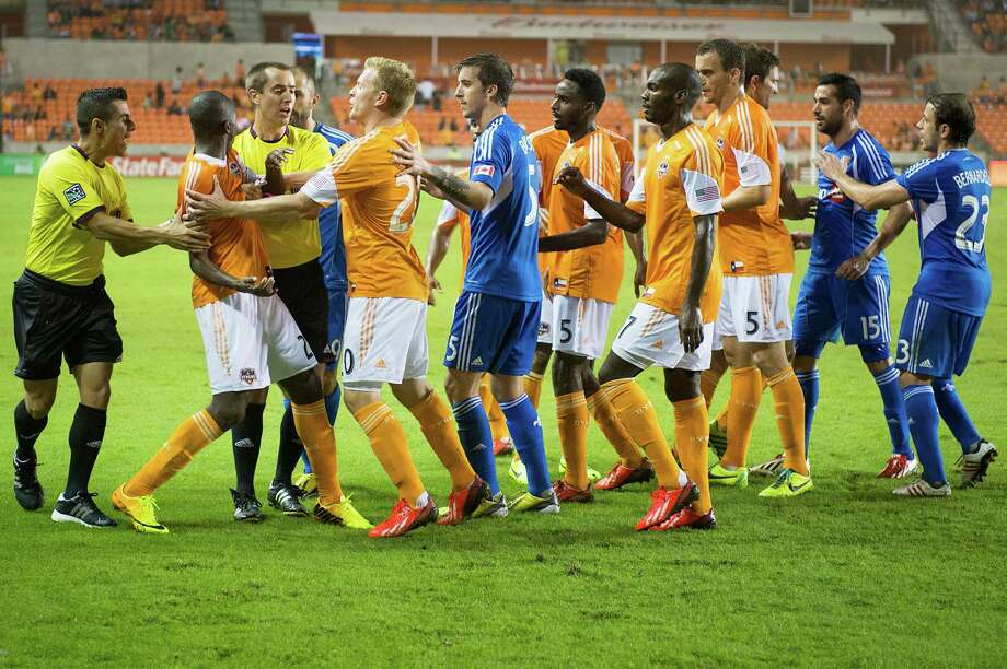 Officials and his teammates separate Dynamo midfielder Boniek Garcia, left, from Impact forward Andres Romero (15) as players scuffle late in the second half. Photo: Smiley N. Pool, Houston Chronicle / © 2013  Houston Chronicle