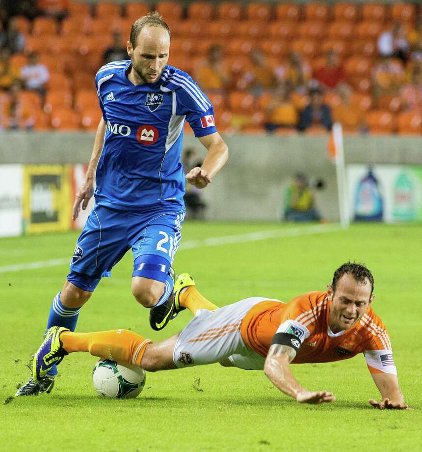Dynamo midfielder Brad Davis is tripped up by Impact midfielder Justin Mapp. Photo: Smiley N. Pool, Houston Chronicle / © 2013  Houston Chronicle