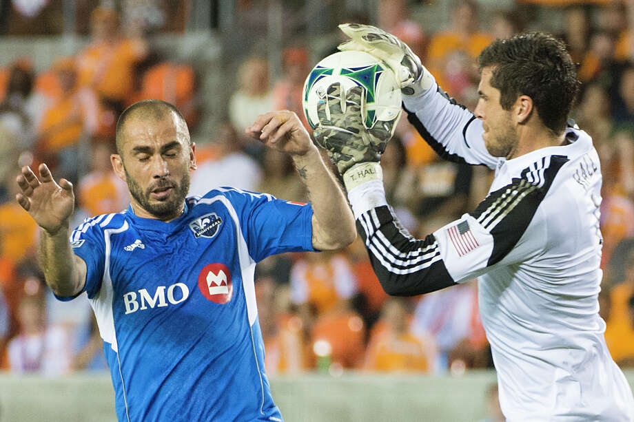 Dynamo goalkeeper Tally Hall takes the ball away from Impact forward Marco Di Vaio during the first half. Photo: Smiley N. Pool, Houston Chronicle / © 2013  Houston Chronicle