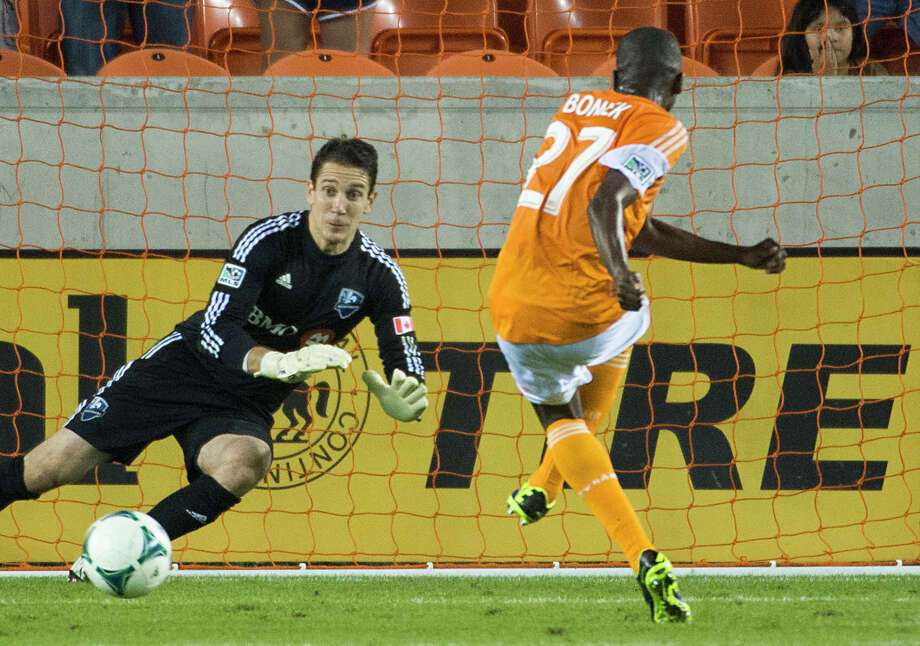 Dynamo midfielder Boniek Garcia beats Impact goalkeeper Troy Perkins to score on a penalty kick during the first half. Photo: Smiley N. Pool, Houston Chronicle / © 2013  Houston Chronicle