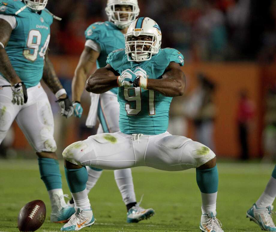 Defensive end Cameron Wake celebrates a first-quarter sack. He also sacked Andy Dalton for the game-winning safety. Photo: Joe Rimkus Jr. / Miami Herald