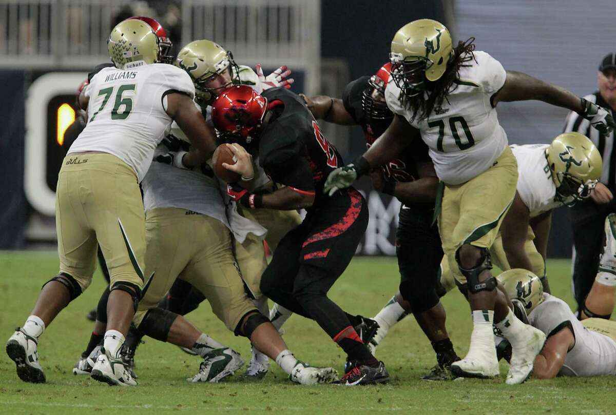 UH defensive end Tyus Bowser, center right, sacks South Florida quarterback Mike White, resulting in a fumble in the fourth quarter.