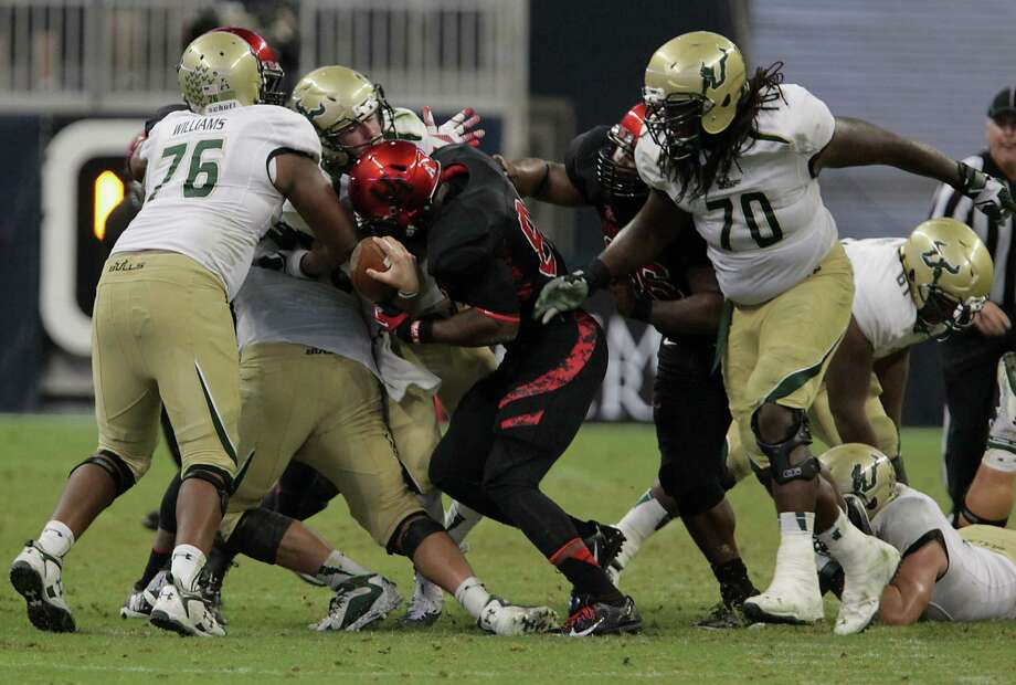 UH defensive end Tyus Bowser, center right, sacks South Florida quarterback Mike White, resulting in a fumble in the fourth quarter. Photo: James Nielsen, Staff / © 2013  Houston Chronicle