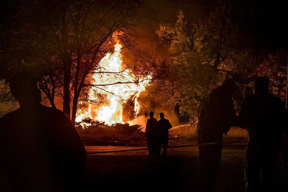 Mayor Dayne Walling, center left, and Police Chief James Tolbert stand on Avenue A as they watch flames take a vacant home while firefighters battle the first blaze on Devil's Night at the intersection of Avenue A and East Dayton Street, Wednesday, Oct. 30, 2013, in Flint, Mich. (AP Photo/The Flint Journal, MLive.com, Jake May) LOCAL TV OUT; LOCAL INTERNET OUT Photo: Jake May, Associated Press