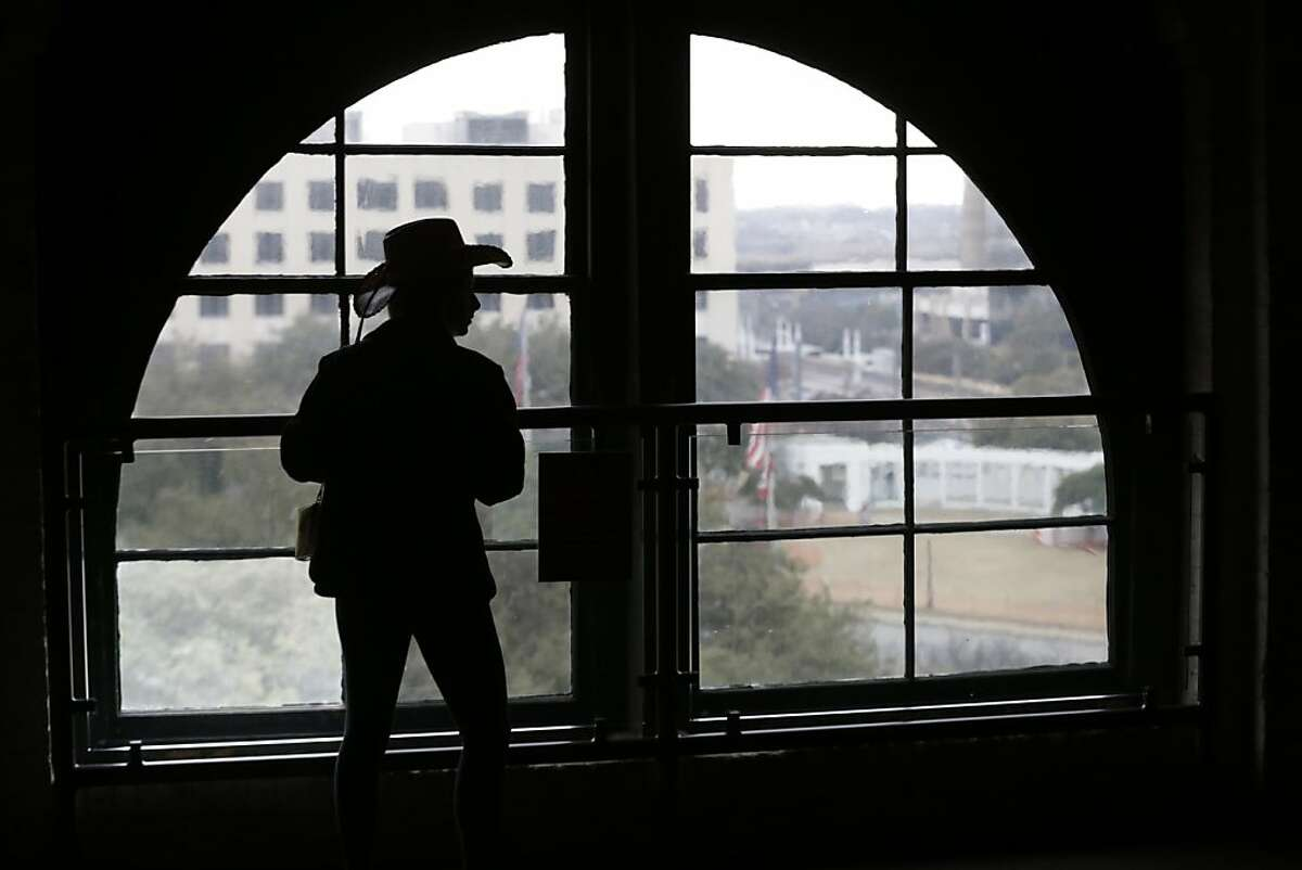 A visitor wearing a cowboy hat looks out onto Dealey Plaza from the Sixth Floor Museum located in the former Texas School Book Depository building in Dallas on Friday, Jan. 25, 2013. As the nation and world mark the 50th anniversary of the assassination of John F. Kennedy, special attention once again falls on Dallas. (AP Photo/LM Otero)