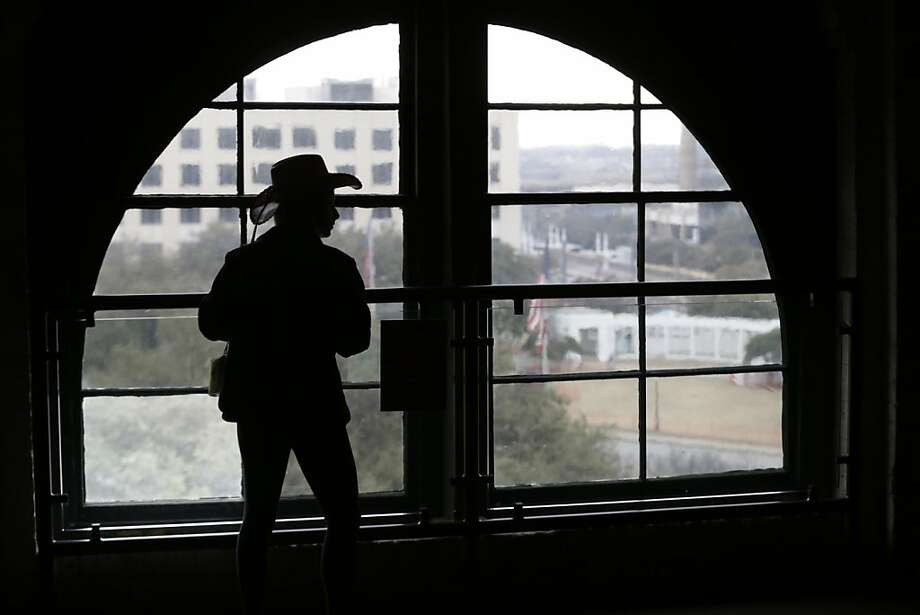 A visitor wearing a cowboy hat looks out onto Dealey Plaza from the Sixth Floor Museum located in the former Texas School Book Depository building in Dallas on Friday, Jan. 25, 2013. As the nation and world mark the 50th anniversary of the assassination of John F. Kennedy, special attention once again falls on Dallas. (AP Photo/LM Otero) Photo: LM Otero, Associated Press