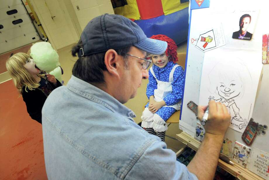 Caricature artist Rich Conley, center, does a drawing of six-year-old Alexis Dievendorf dress as Raggedy Ann during the Elsmere Fire department's Halloween party on Thursday Oct. 31, 2013 in Delmar, N.Y. (Michael P. Farrell/Times Union) Photo: Michael P. Farrell / 00024477A