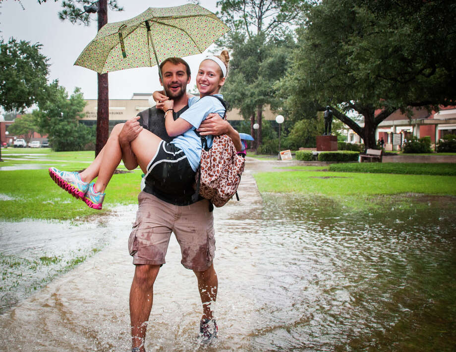 Blake Borman carries Alyse Hanks across a flooded Lamar University on Thursday. Michael Reed Photo: Michael Reed / Michael Reed