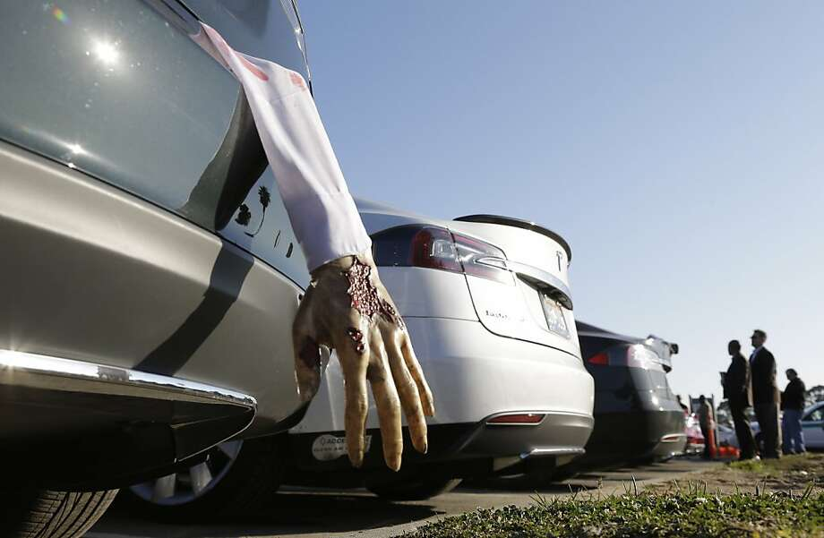 An artificial hand for Halloween hangs out the back of a Tesla Motors Model S electric sedan during a demonstration Thursday, Oct. 31, 2013, at Crissy Field in San Francisco.  Photo: Eric Risberg, Associated Press