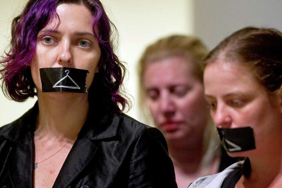 Karen Rayne, left, protests Governor Rick Perry's signing of HB2 in the Capitol Extension Auditorium on Thursday, July 18, 2013. He signed the stricter abortion regulations into law Thursday morning as supporters cheered and faint chants of 'shame' could be overheard from protesters outside the Capitol auditorium.  Photo: Laura Skelding, Austin American-Statesman / Austin American-Statesman