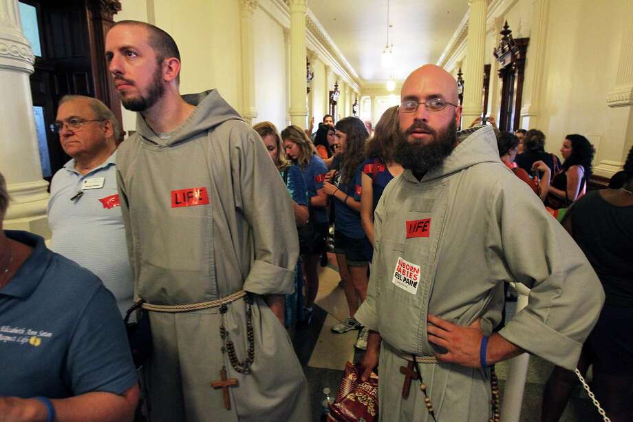 Father Jeremiah Shryock and Brother Seamus Laracy wait in line to get into the Senate as demonstrators voice their opinion as the Capitol building fills before the Senate debates passage of abortion legislation on July 12, 2013. Photo: TOM REEL