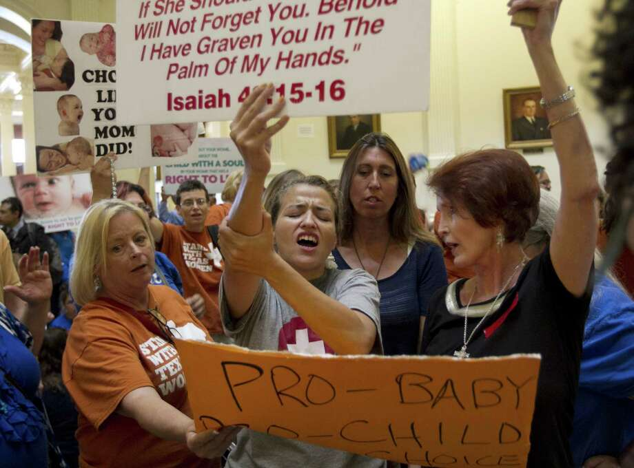 Abortion opponent Katherine Aguillar, middle, struggles to keep her sign raised during demonstrations at the Capitol in Austin, Texas, while the Texas Senate debates the abortion restriction bill, House Bill 2, on Friday July 12, 2013. Photo: Jay Janner, McClatchy-Tribune News Service / Austin American-Statesman