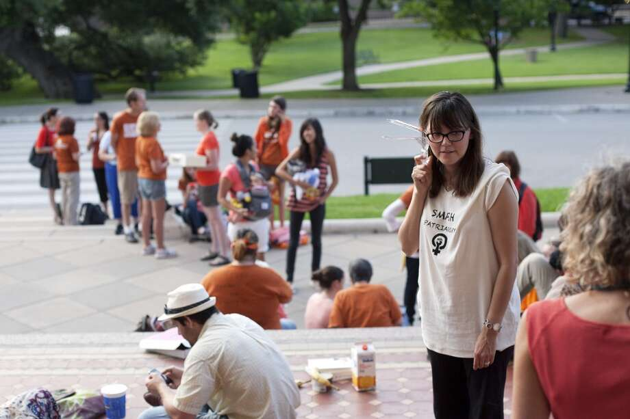 Kristi Lara holds a gynecological speculum as she and dozens of others wait for the Texas State Capitol to open its doors at 7 a.m., in Austin, Texas, Friday, July 12, 2013. Many demonstrators brought gynecological devices to the Capitol to symbolically personalize women's issues. The Texas Senate's leader, Lt. Gov. David Dewhurst, has scheduled a vote for Friday on the same restrictions on when, where and how women may obtain abortions in Texas that failed to become law after a Democratic filibuster and raucous protesters were able to run out the clock on an earlier special session. (AP Photo/Tamir Kalifa) Photo: Tamir Kalifa, Associated Press