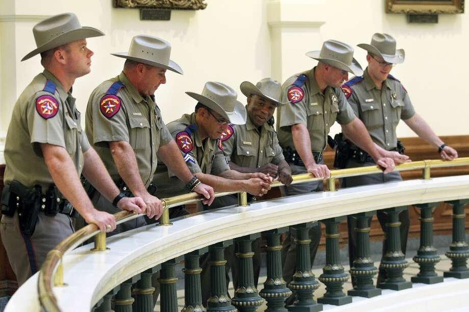 DPS troopers keep an eye on protestors congregating in the rotunda area  in the state capitol building on July 10, 2013.