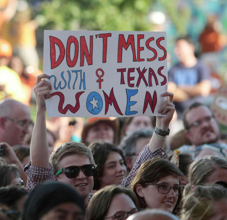 A rally partcipant holds up a sign during the Planned Parenthood Action Fund's Stand with Texas Women Rally at Discovery Green in Houston, Texas. The Rally highlighted the abortion restriction bill, House Bill 2 being Pushed in Austin Tuesday, July 9, 2013, in Houston. (AP Photo/Houston Chronicle, Billy Smith II) Photo: Billy Smith II, ASSOCIATED PRESS / 2013 HOUSTON CHRONICLE2013