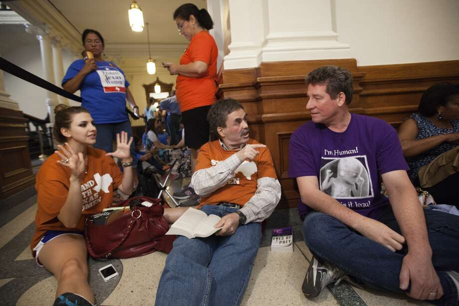Pro-choice supporters Jessica Nenow, left, and Art Stretton, center, debate abortion rights with Brian McAuliffe, who is against abortions, while waiting in line to enter the Senate gallery at the Texas State Capitol in Austin, Texas, Friday, July 12, 2013. Texas Senate leader, Lt. Gov. David Dewhurst has scheduled a vote for Friday on the same restrictions on when, where and how women may obtain abortions in Texas that failed to become law after a Democratic filibuster and raucous protesters were able to run out the clock on an earlier special session. (AP Photo/Tamir Kalifa) Photo: Tamir Kalifa, Associated Press