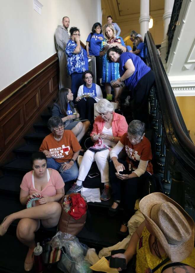 Supporters and opponents of an abortion bill pass time as they wait in line outside the Texas Senate chambers as he final vote by the Senate is expected to begin, Friday, July 12, 2013, in Austin, Texas. The bill would require doctors to have admitting privileges at nearby hospitals, only allow abortions in surgical centers, dictate when abortion pills are taken and ban abortions after 20 weeks. (AP Photo/Eric Gay) Photo: Eric Gay, Associated Press
