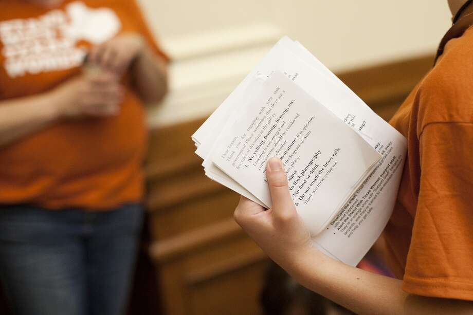 Decorum cards are distributed to people waiting in line to enter the Senate Gallery in the State Capitol in Austin, Texas on Friday, July 12, 2013. The Texas Senate's leader, Lt. Gov. David Dewhurst, has scheduled a vote for Friday on the same restrictions on when, where and how women may obtain abortions in Texas that failed to become law after a Democratic filibuster and raucous protesters were able to run out the clock on an earlier special session. (AP Photo/Tamir Kalifa) Photo: Tamir Kalifa, Associated Press