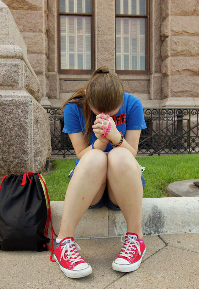 Abortion opponent Madison Salmons, right, 14, of Mesquite, Texas, prays outside the Capitol in Austin, Texas on Tuesday July 9, 2013, as the Texas House debated tough new abortion restrictions prior to taking part in a planned vote on the measure. (AP Photo/Austin American-Statesman, Jay Janner) Photo: Jay Janner, AP / Austin American-Statesman