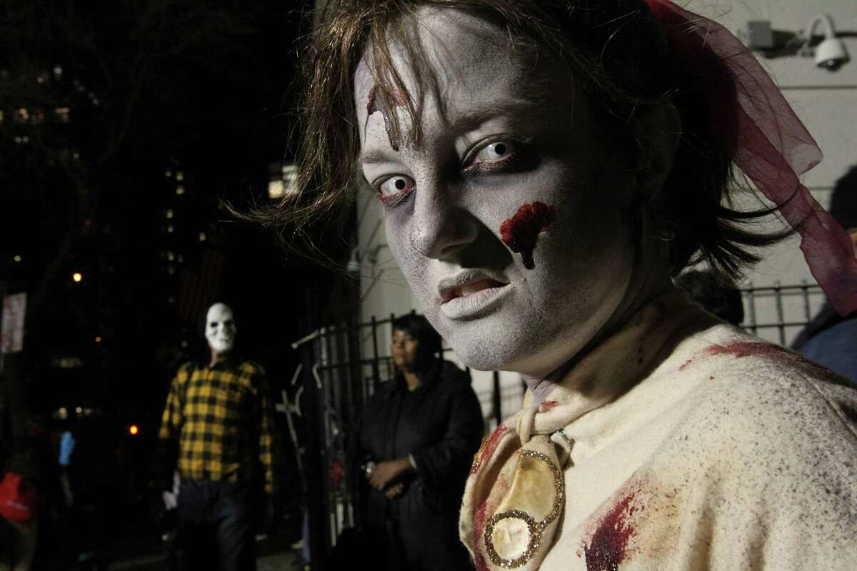 Dressed as a zombie, Christina Dunham, foreground, poses for photographs as she waits to take part in the Village Halloween Parade Thursday Oct. 31, 2013 in New York. (AP Photo/Tina Fineberg) ORG XMIT: NYTF103
