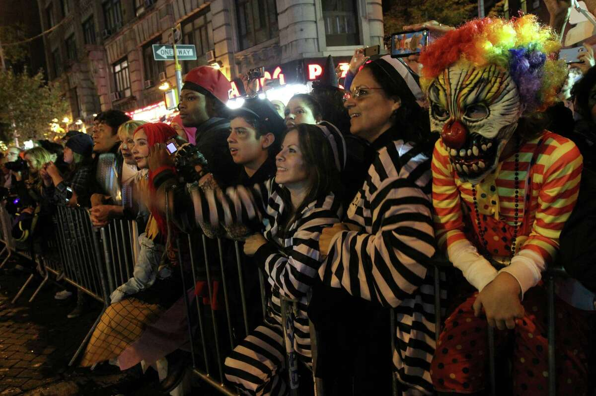 Spectators, some dressed for the occasion, including Louis Topi, 8, from France, right, watch as the Village Halloween Parade makes its up New York's Sixth Avenue Thursday Oct. 31, 2013. (AP Photo/Tina Fineberg) ORG XMIT: NYTF104