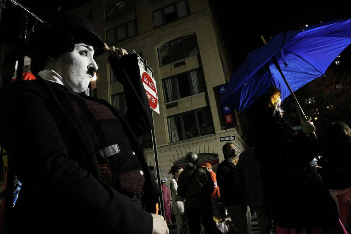 Dressed as Charlie Chaplin, Rachel Kambury, of the Brooklyn borough of New York, left, poses for photographs as she waits to take part in the Village Halloween Parade Thursday Oct. 31, 2013 in New York. (AP Photo/Tina Fineberg) ORG XMIT: NYTF102