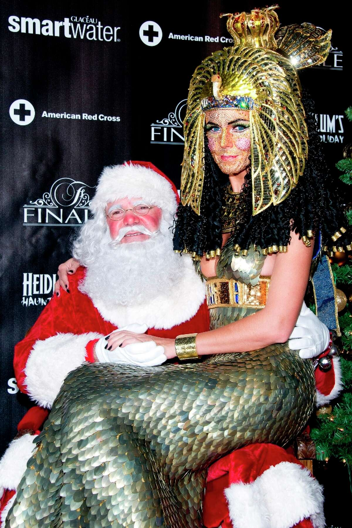 Heidi Klum, dressed as Cleopatra, poses with Santa Claus during her Haunted Holiday Party benefiting Superstorm Sandy relief efforts, on Saturday, Dec. 1, 2012 in New York.