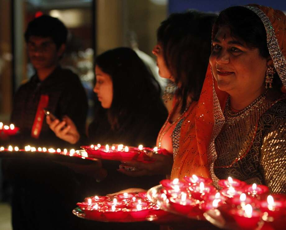 Participants hold plates of lit diyas, or candles, during Diwali, an Indian festival also known as the festival of lights, at Hemisfair Plaza on Saturday, Nov. 6, 2010. Diyas signify the triumph of good over evil. Photo: Michael Miller, Express-News