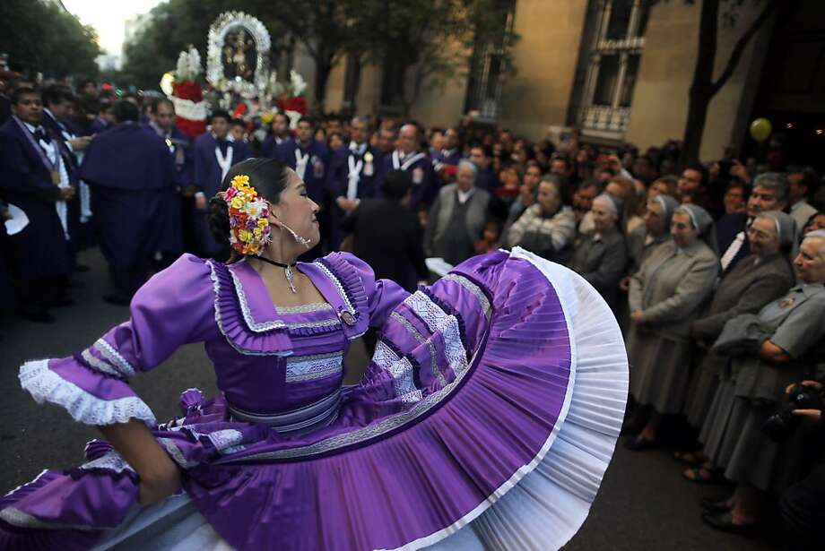 "Nuns watch a woman dancing in a procession in Madrid honoring ""The Lord of Miracles,"" a Catholic icon believed to have curing and protective powers. Photo: Andres Kudacki, Associated Press"