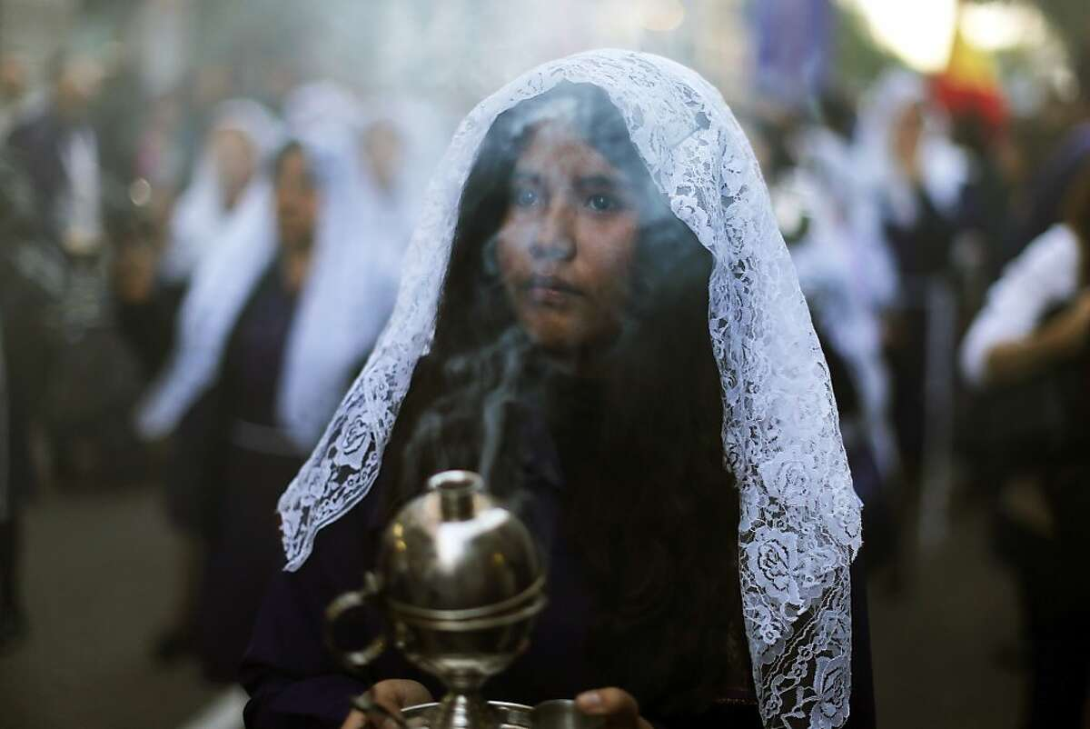 Women participate in a procession honoring The Lord of Miracles