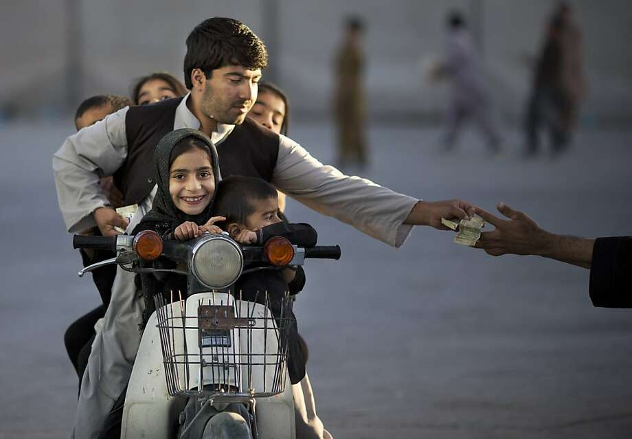 An Afghan man with his five children on his motorbike pays money to enter a park in Kandahar, southern Afghanistan, Friday, Nov 1, 2013. On Fridays, the Islamic day of rest and prayer, children and their families traditionally gather in one of the few parks.  Photo: Anja Niedringhaus, Associated Press